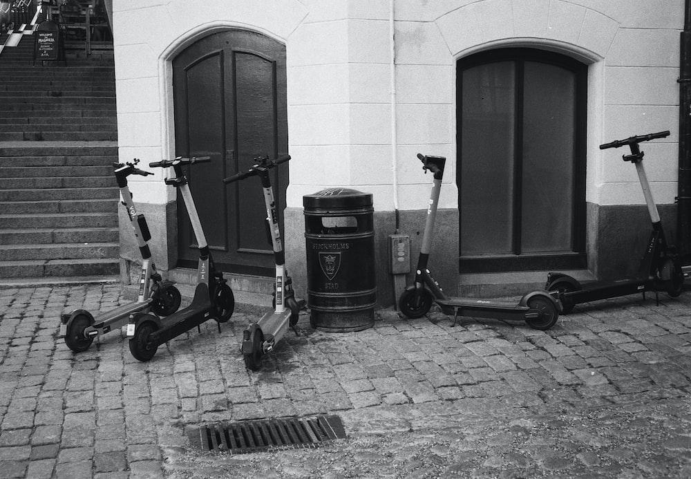 black and gray kick scooter beside black wooden door