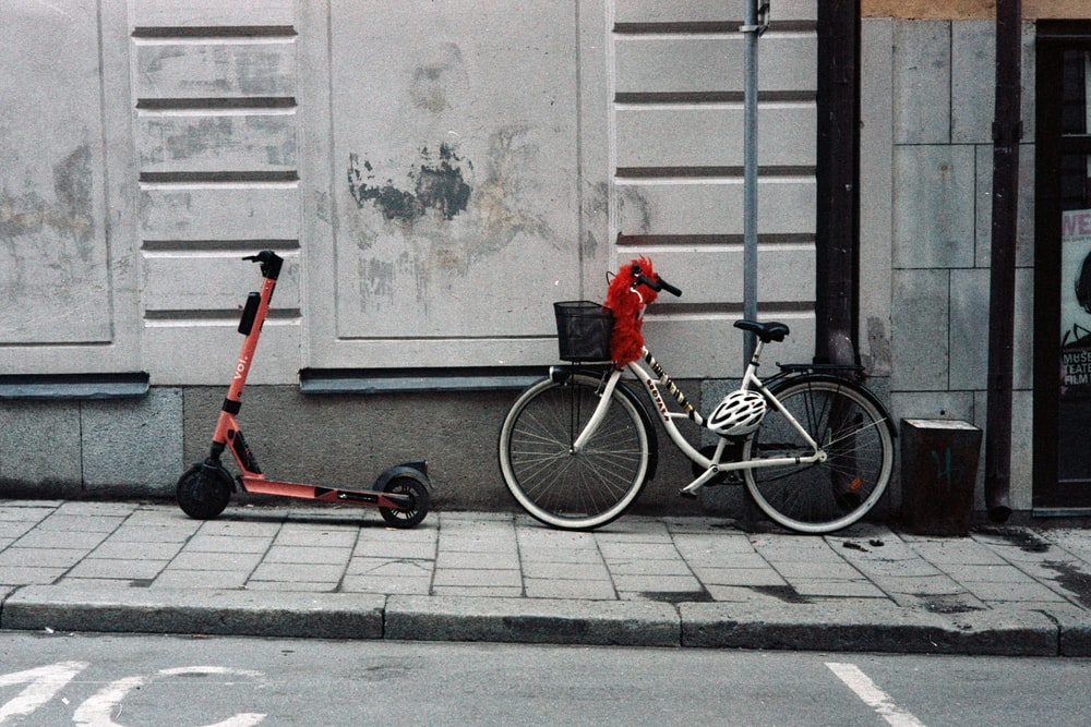 red and black bicycle with training wheels beside white wall