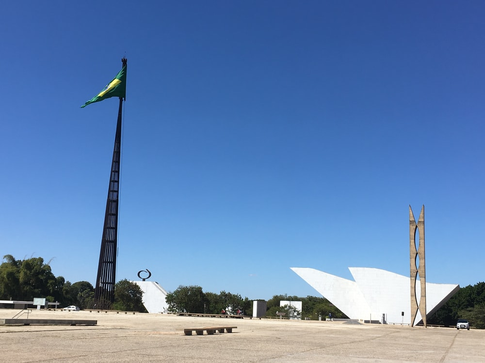 white and green flag on brown field under blue sky during daytime