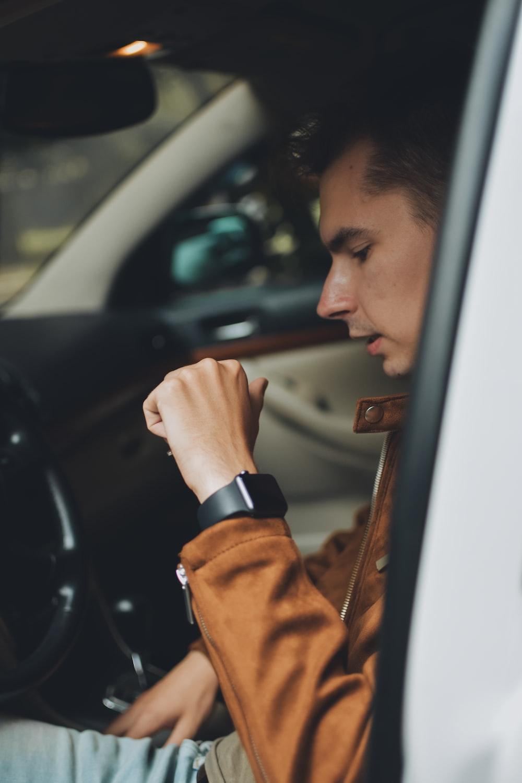 man in brown jacket holding car door