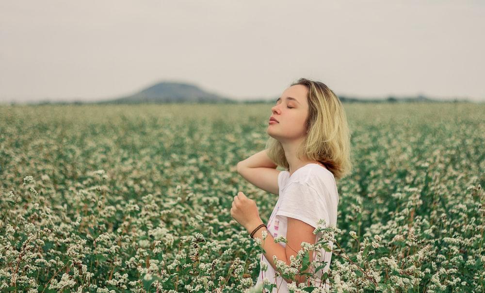 girl in white shirt on flower field during daytime