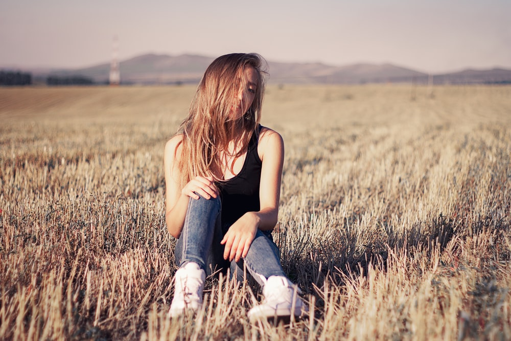 woman in black tank top and blue denim jeans sitting on brown grass field during daytime