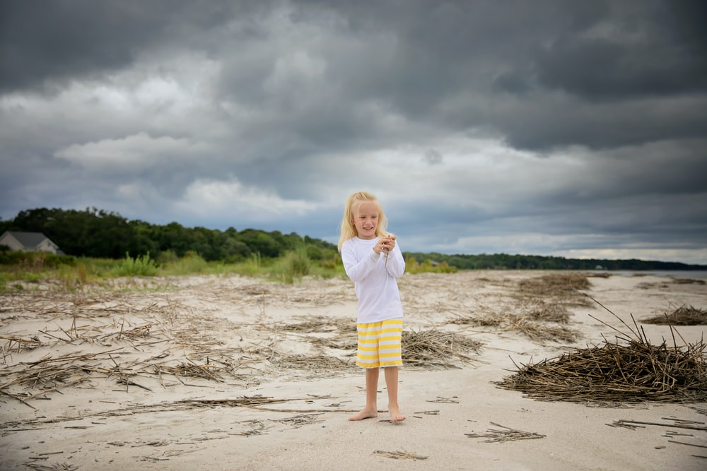 girl in white long sleeve shirt and yellow skirt standing on beach during daytime