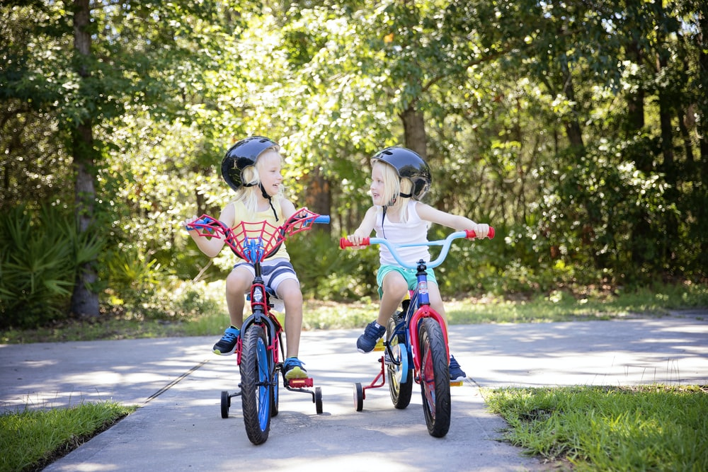 3 year old girls are riding with bikes with training wheels on.