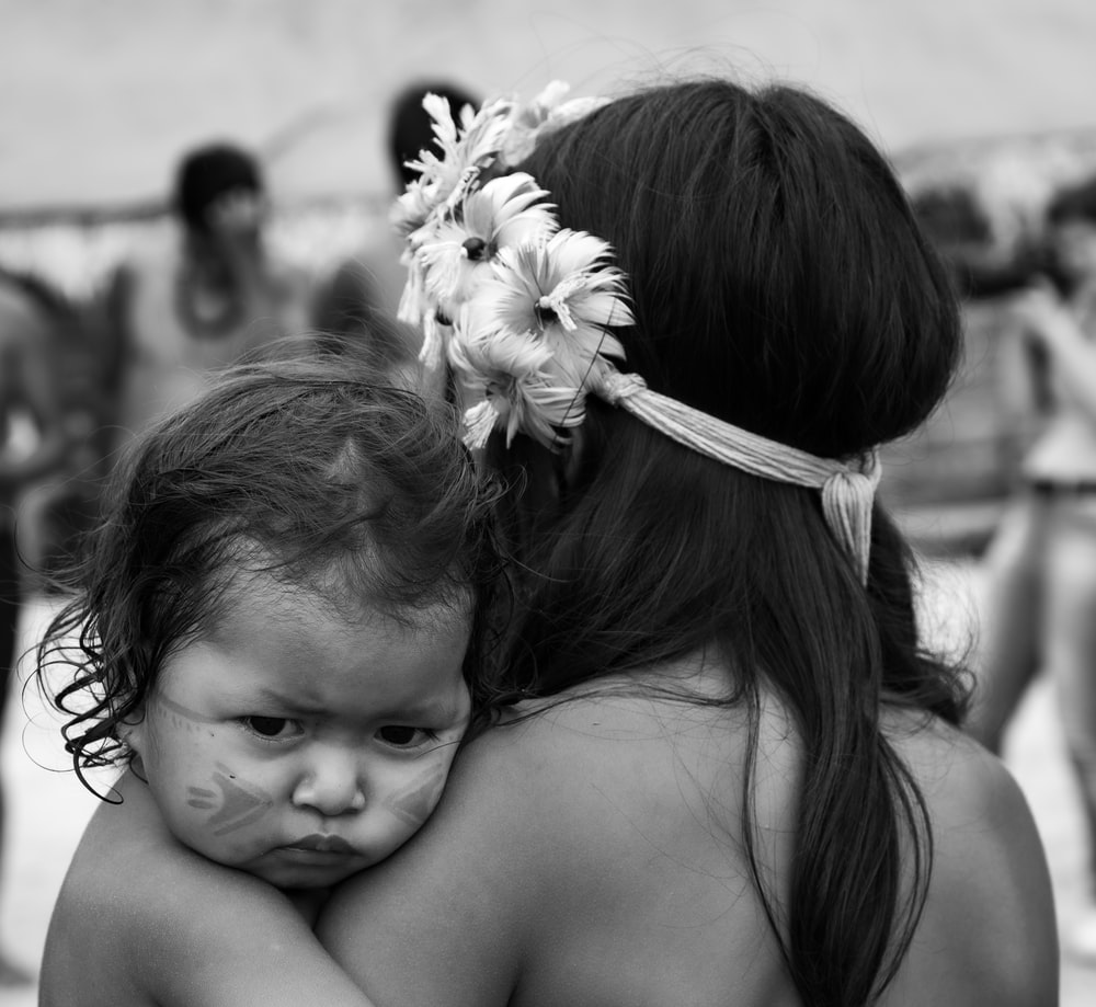 grayscale photo of woman carrying baby