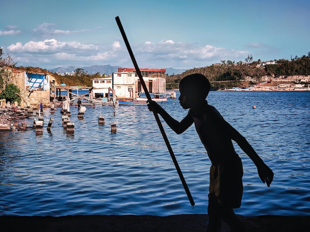 man in black shirt fishing on water during daytime