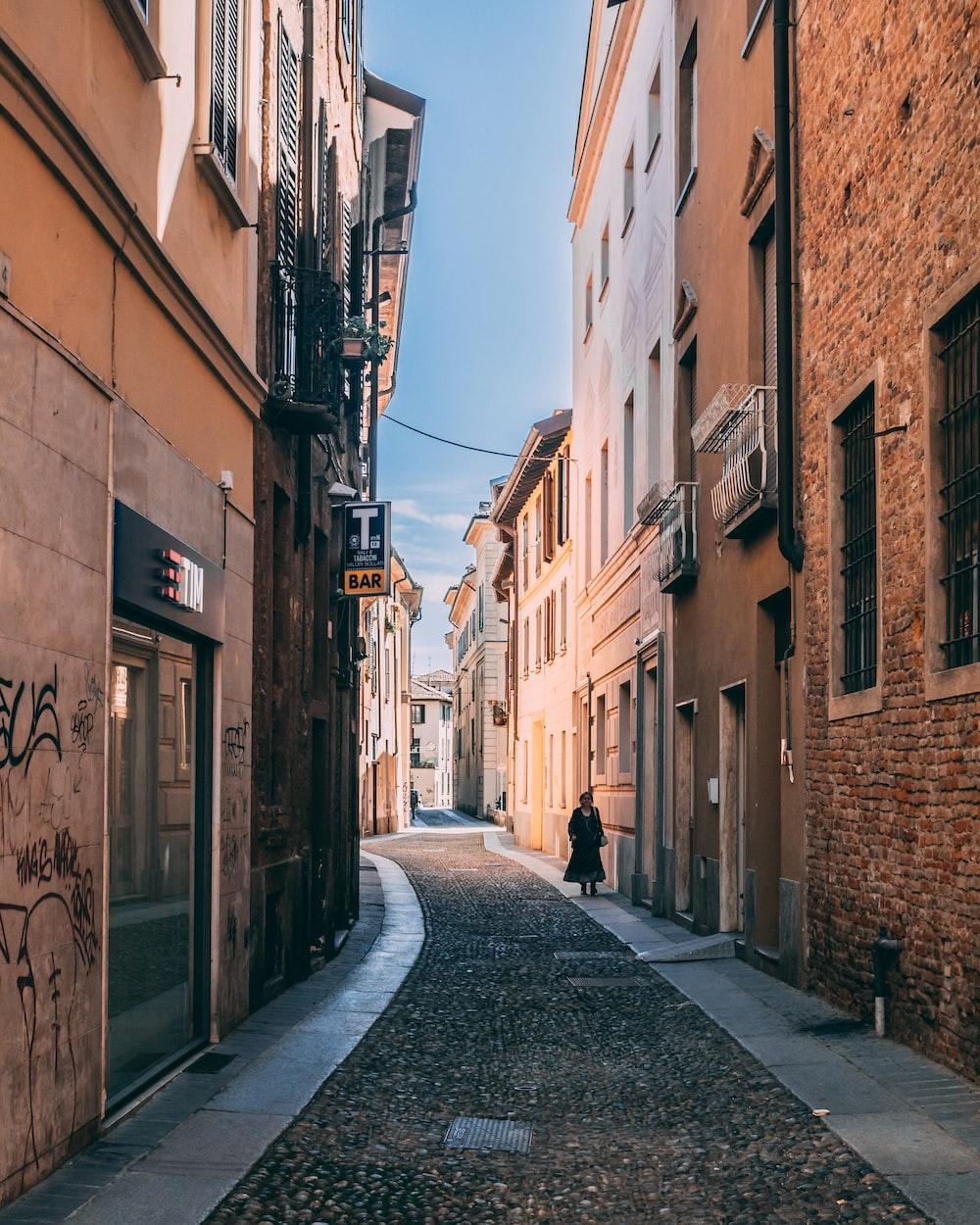 empty street between concrete buildings during daytime