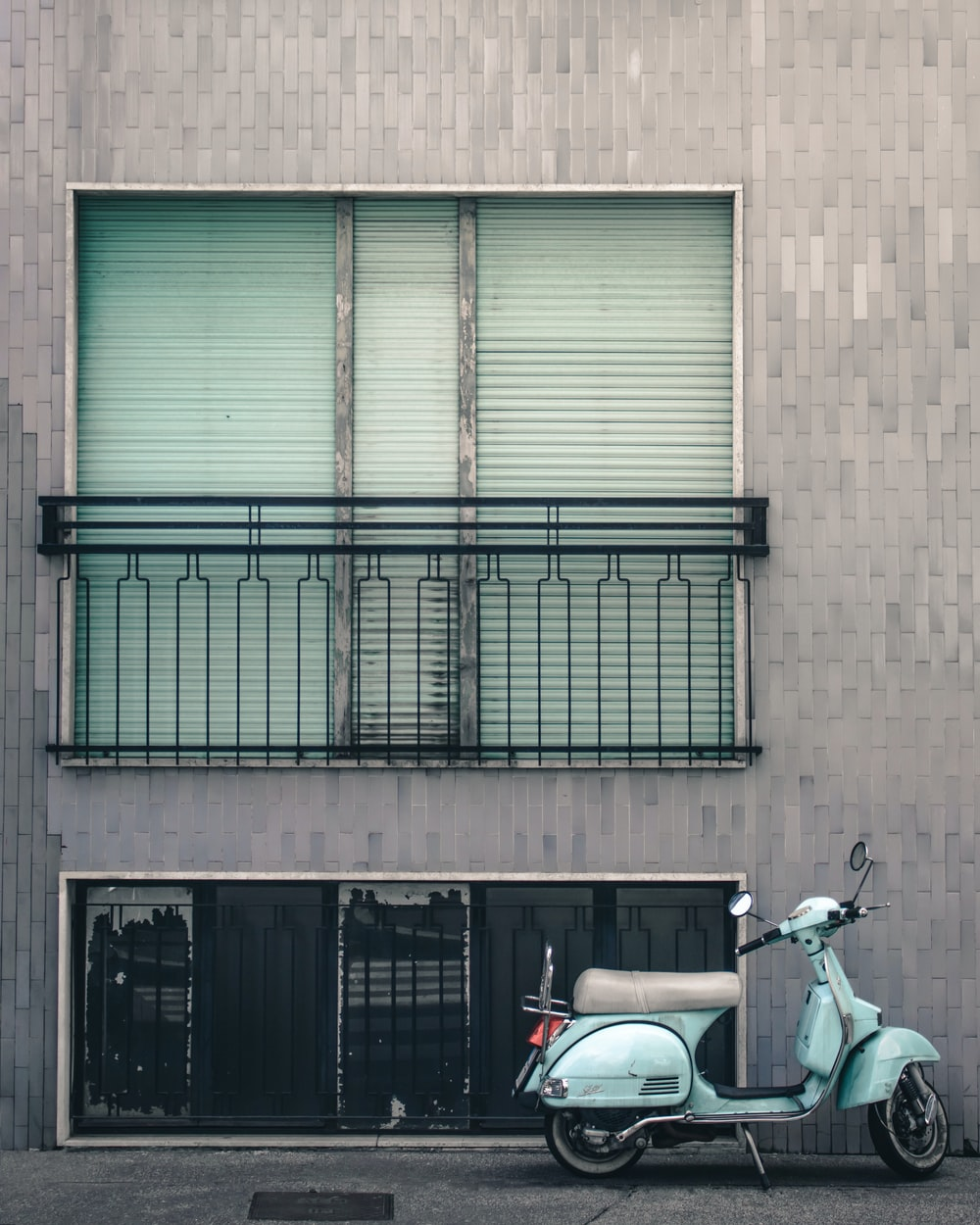 white and black motorcycle parked beside brown building