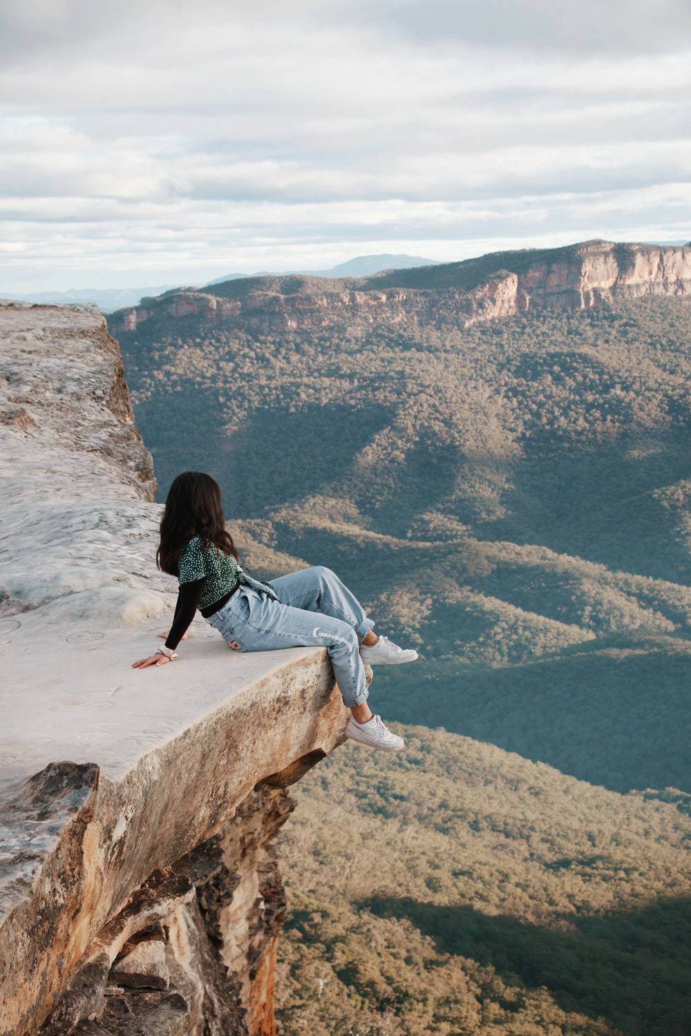 woman in blue denim jeans sitting on brown rock formation during daytime