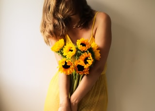 woman in yellow sleeveless dress holding yellow flower bouquet