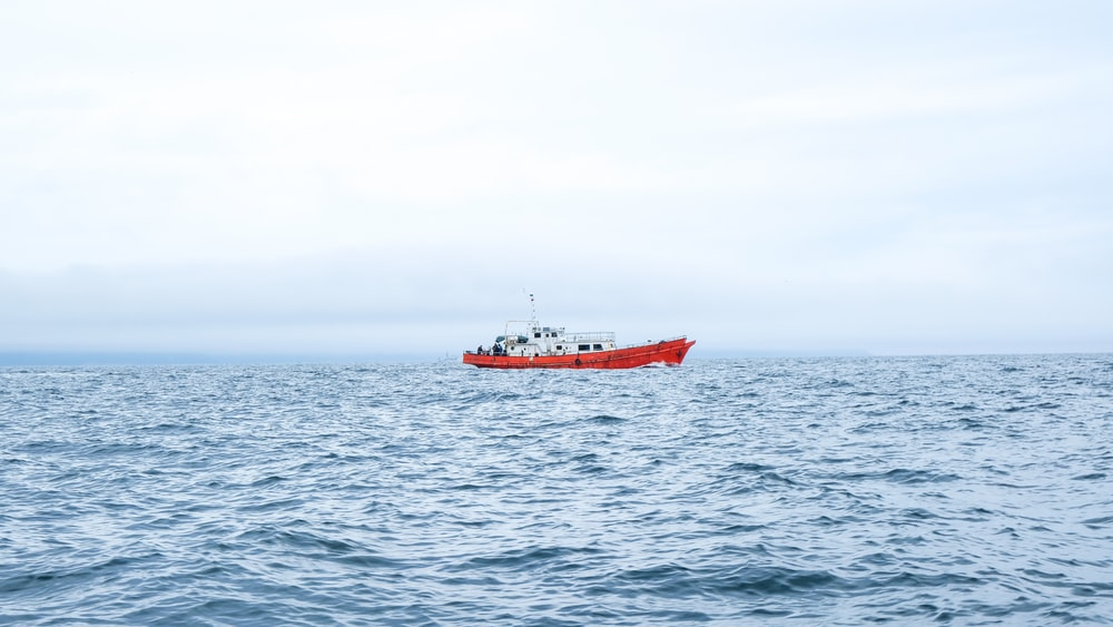 red and white ship on sea under white sky during daytime