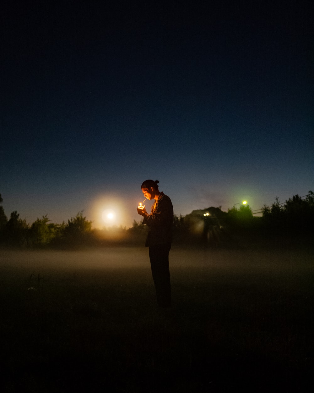 man in black jacket standing on green grass field during night time