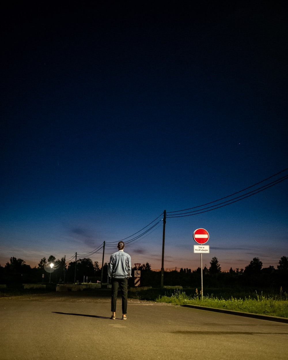 man in white shirt standing on the street during night time