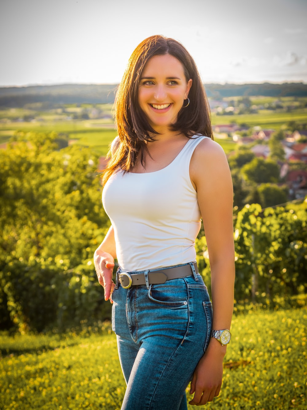 woman in white tank top and blue denim shorts standing on green grass field during daytime