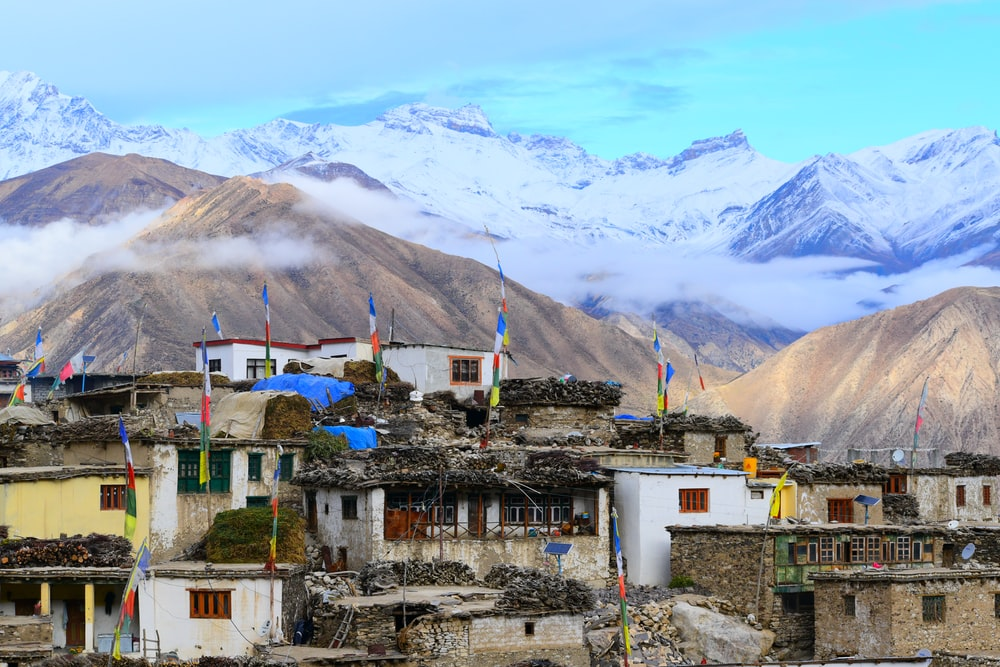 white and brown concrete houses near mountain under white clouds during daytime