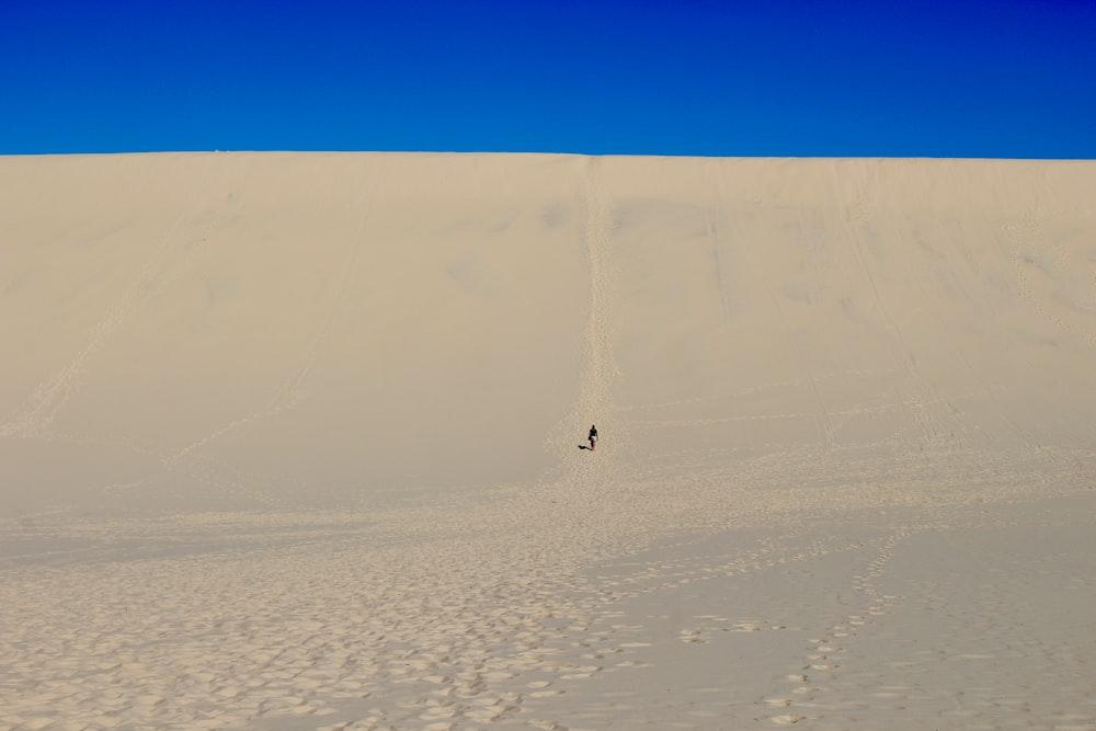 person walking on white sand during daytime