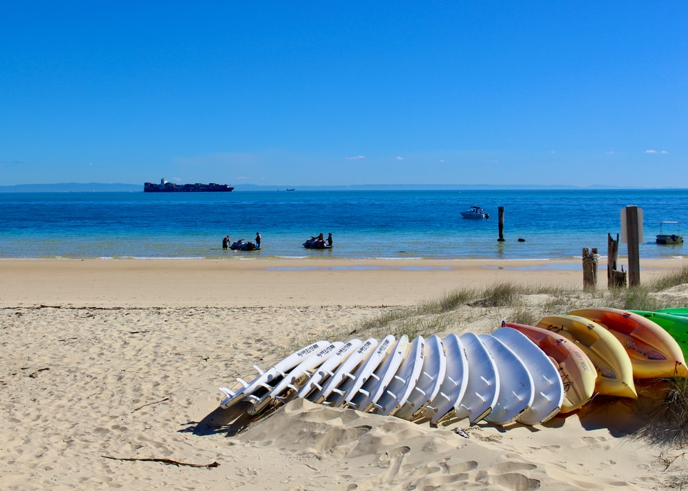 white plastic chairs on beach during daytime