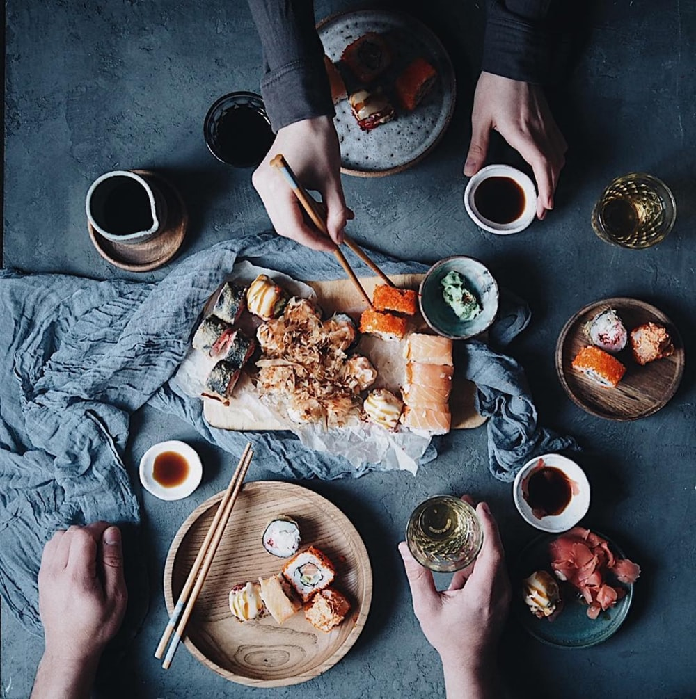 person holding chopsticks and bowl with food