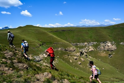 people hiking on green grass field during daytime lesotho teams background