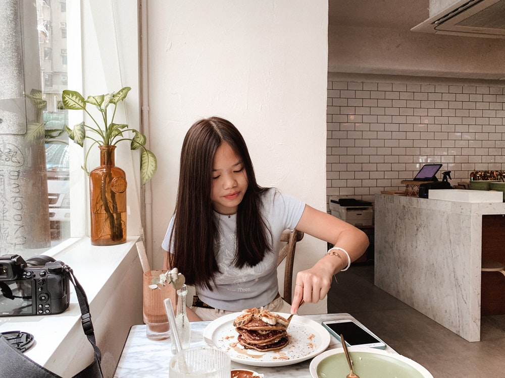woman in gray shirt sitting on chair in front of table with food
