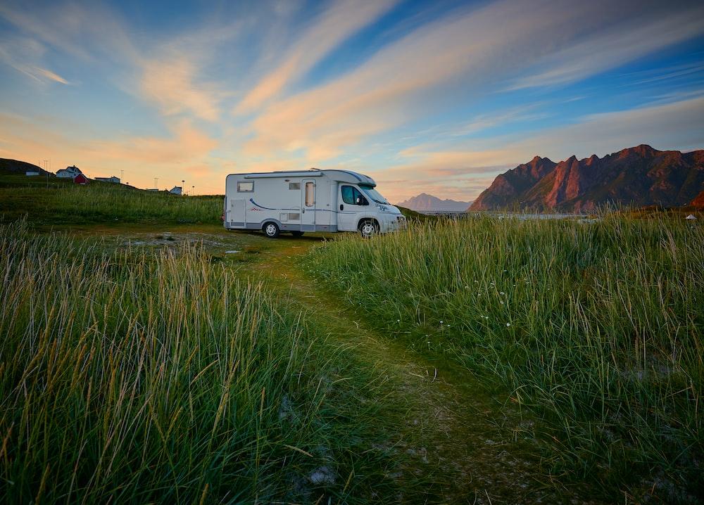 white van on green grass field near brown mountain under blue sky during daytime