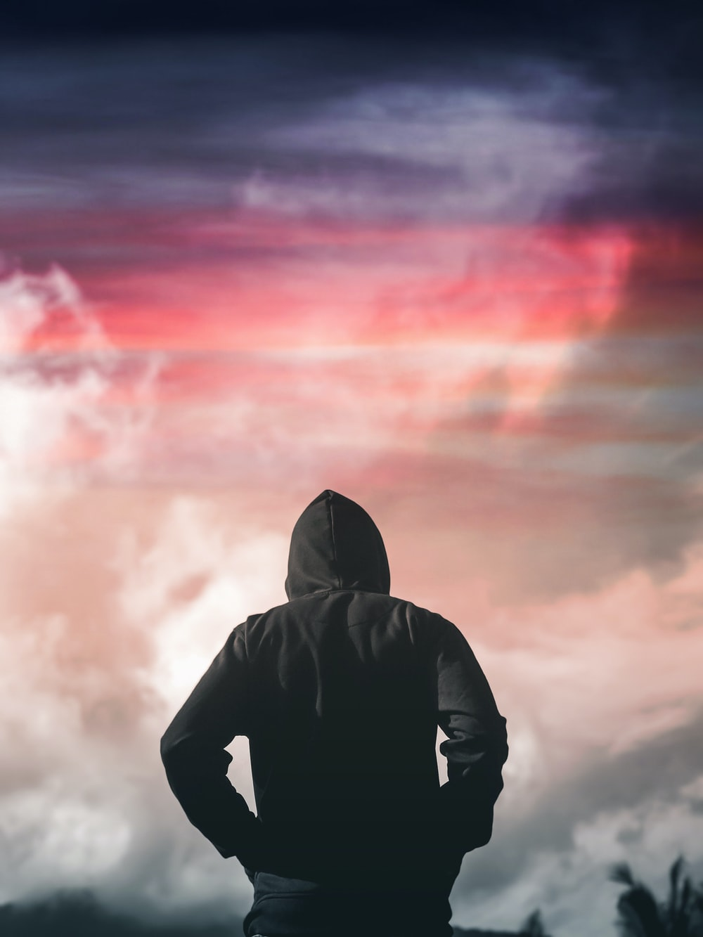 person in black hoodie standing under cloudy sky during daytime
