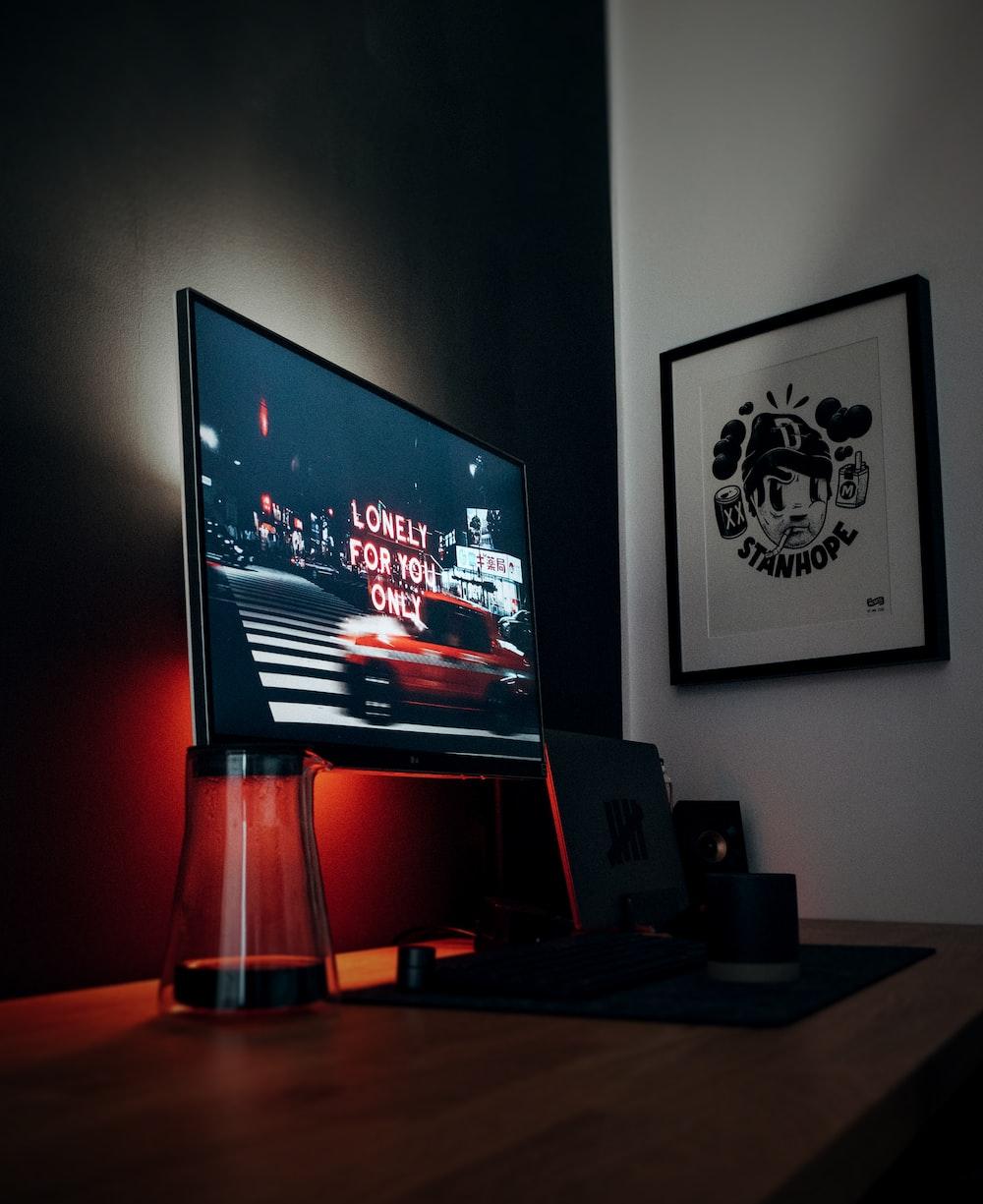 black flat screen tv turned on near black speaker