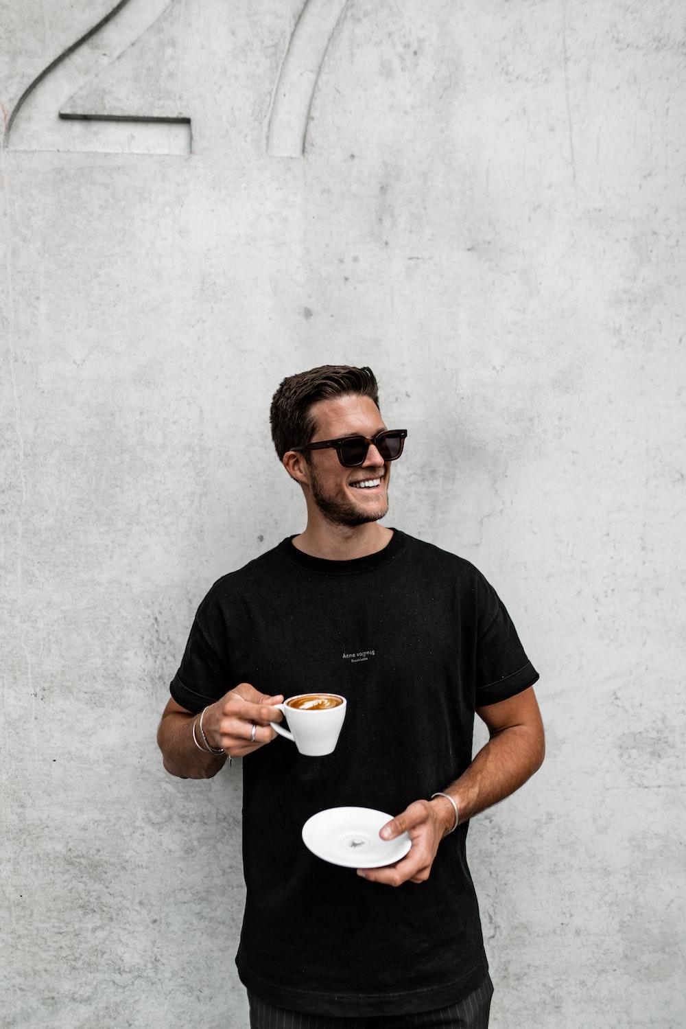 man in black crew neck t-shirt holding white ceramic mug