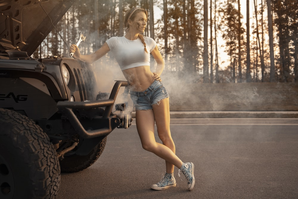 woman in white tank top and blue denim shorts standing on black motorcycle during daytime
