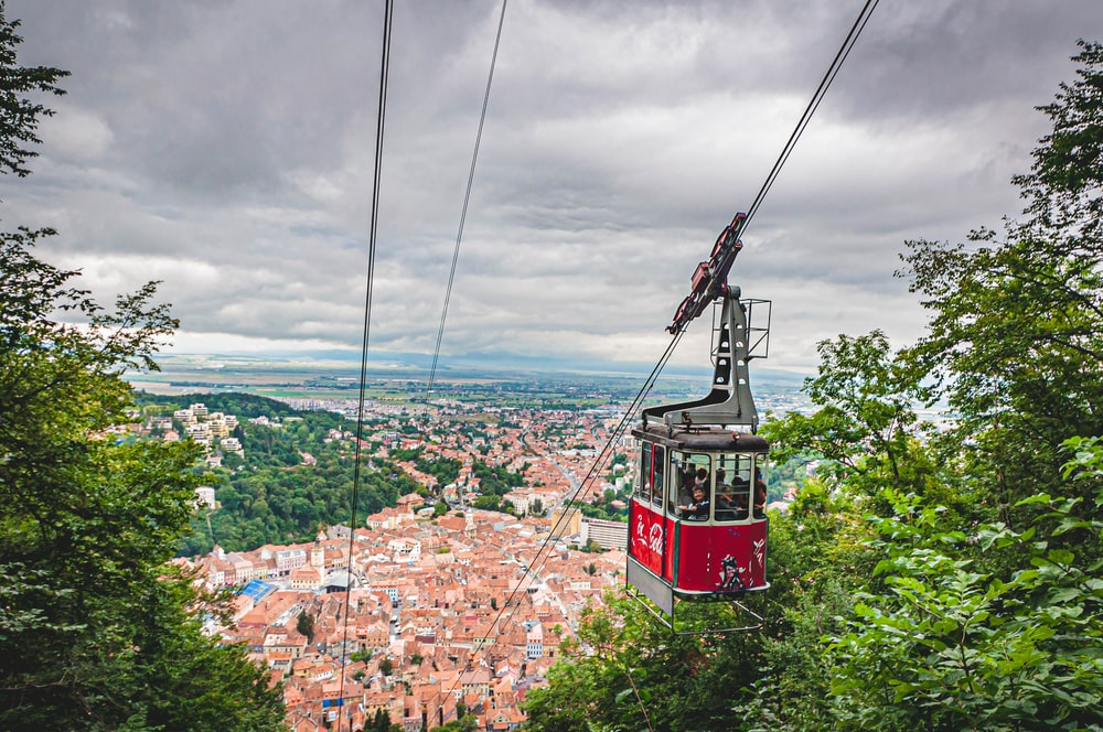 red cable car over city buildings during daytime