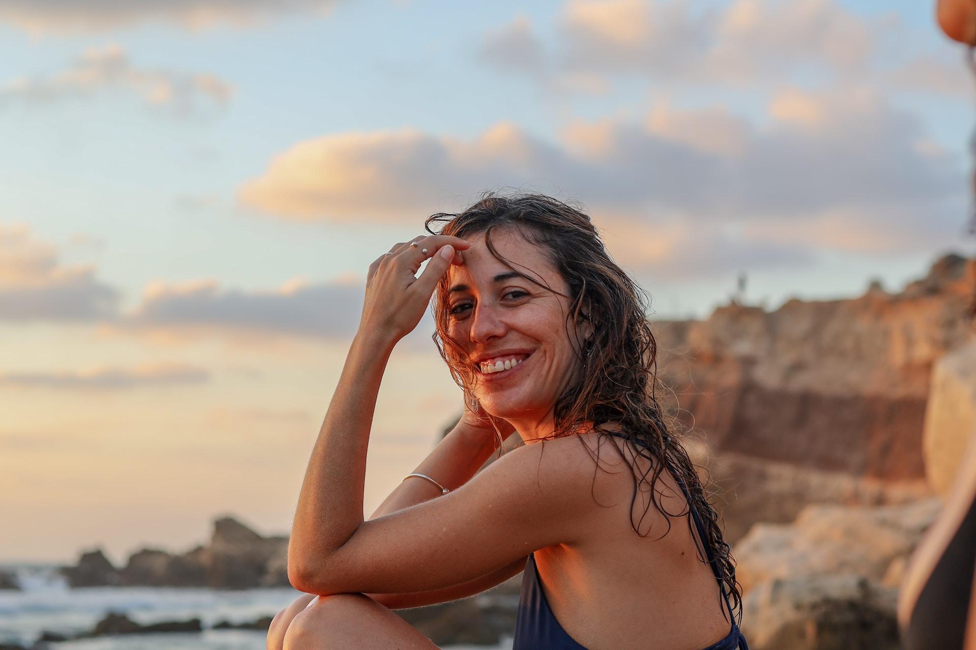 woman in blue bikini sitting on rock during daytime