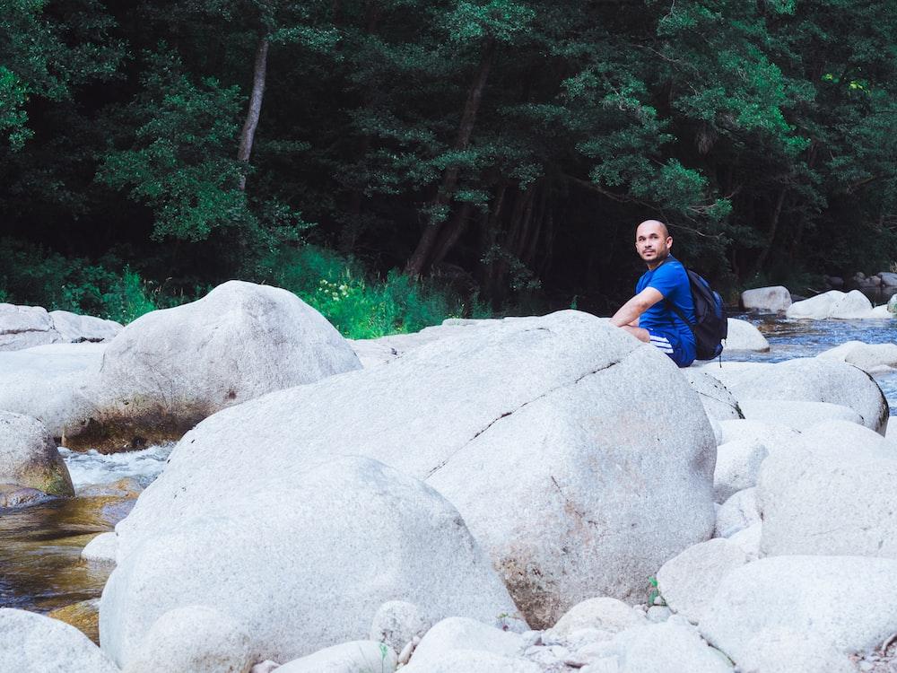 man in blue t-shirt sitting on gray rock