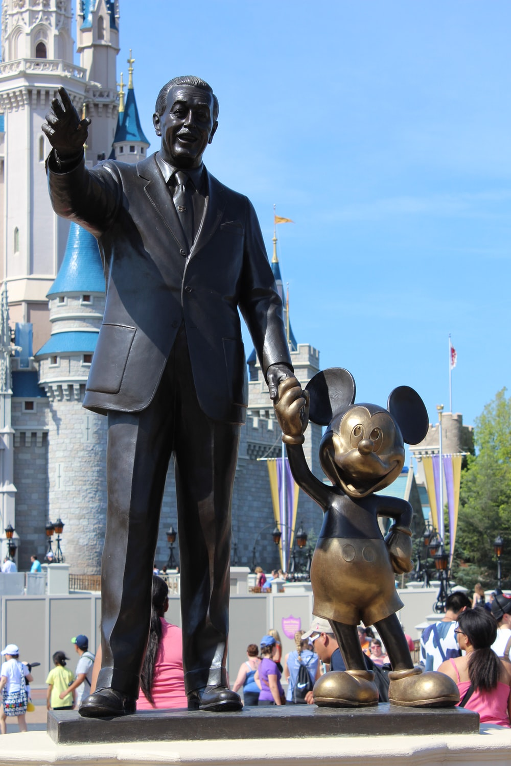 man in black suit standing beside man statue during daytime