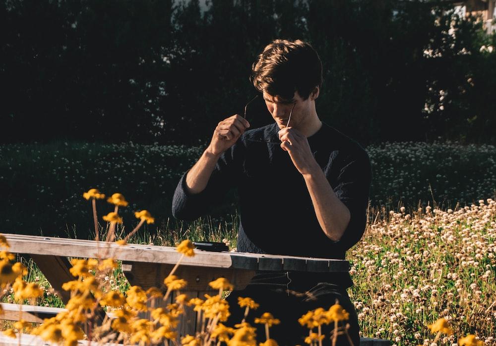 man in black t-shirt sitting on green grass field during daytime