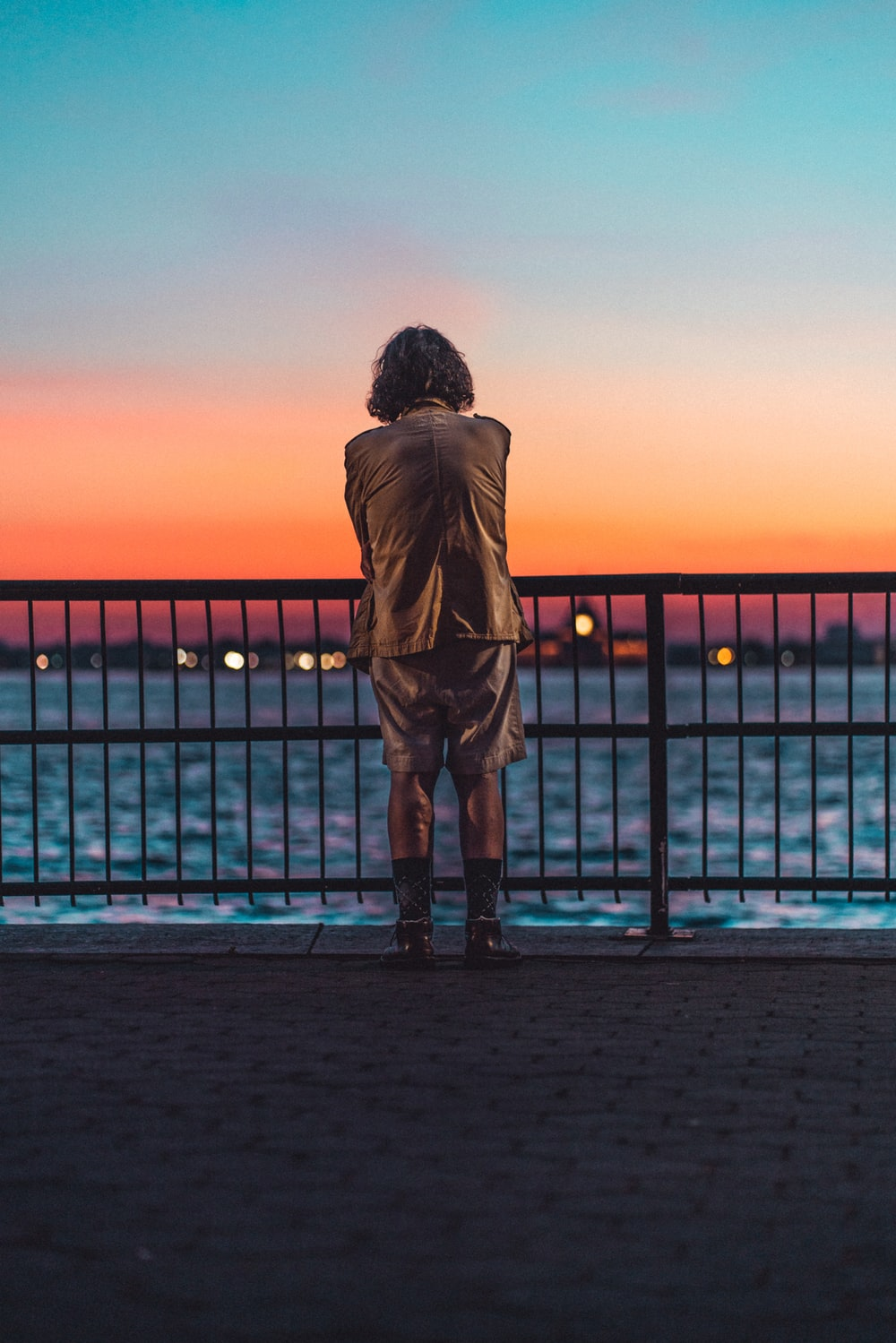 silhouette of person standing on dock during sunset