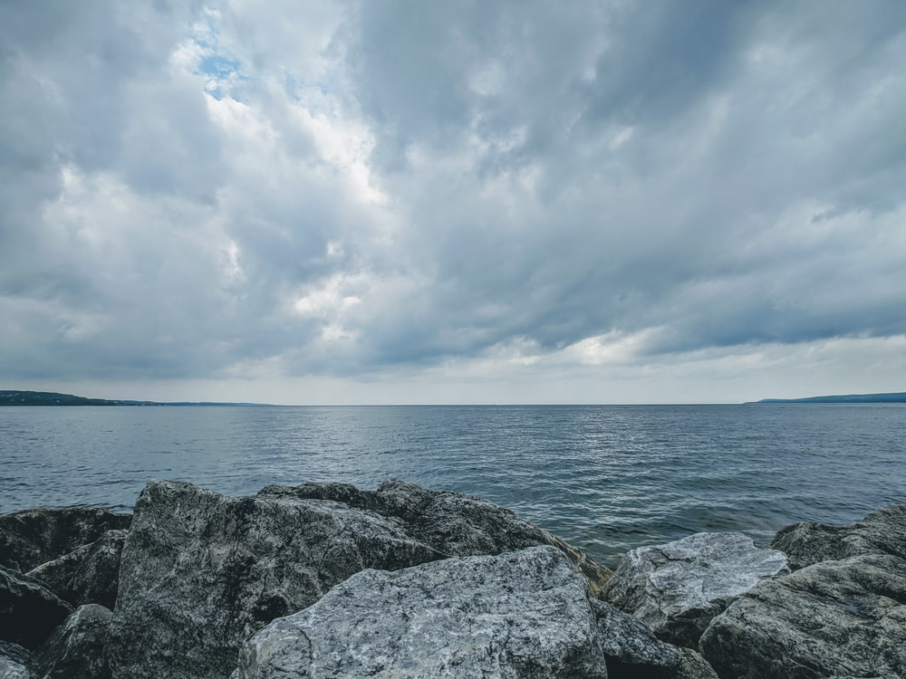 gray rocky shore under white clouds and blue sky during daytime