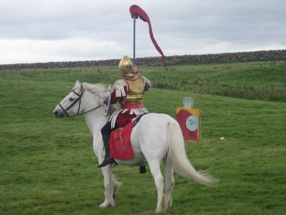 man in white cowboy hat riding white horse during daytime