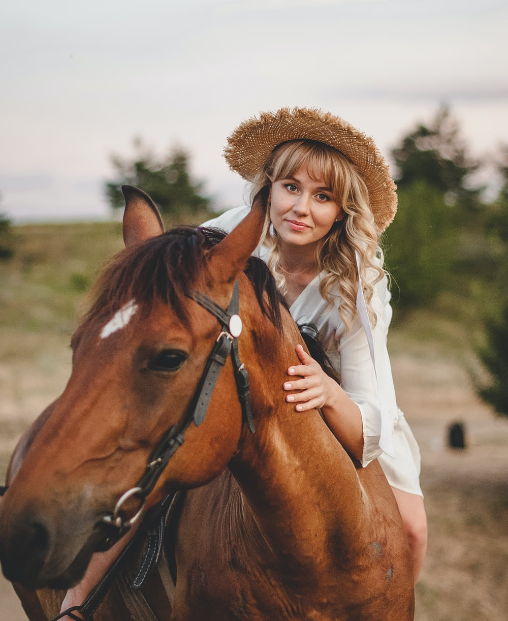 woman in white long sleeve shirt and brown hat standing beside brown horse during daytime