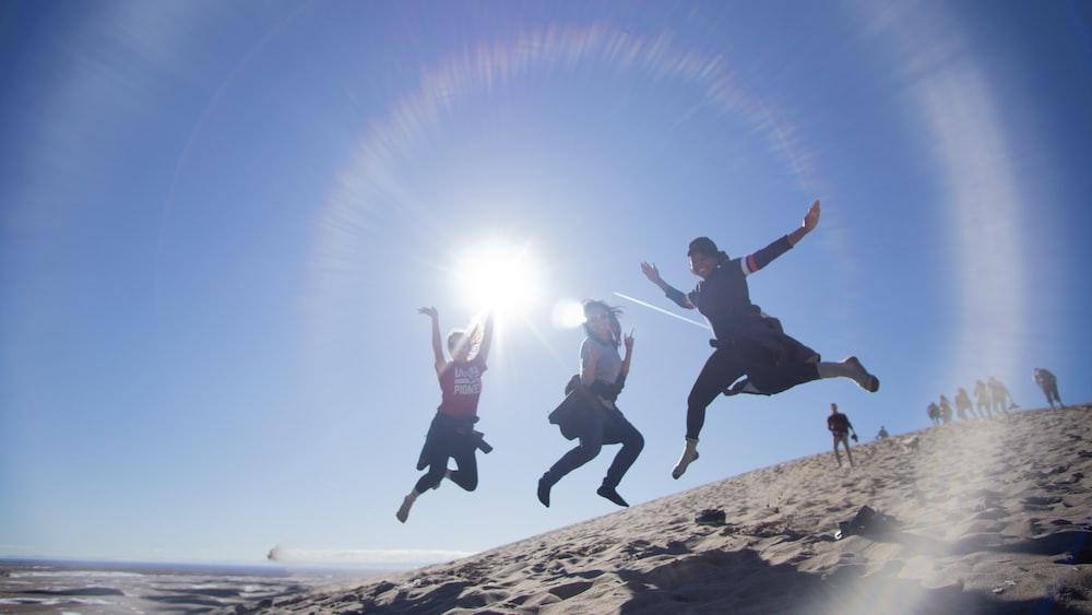 2 men jumping on brown rock during daytime