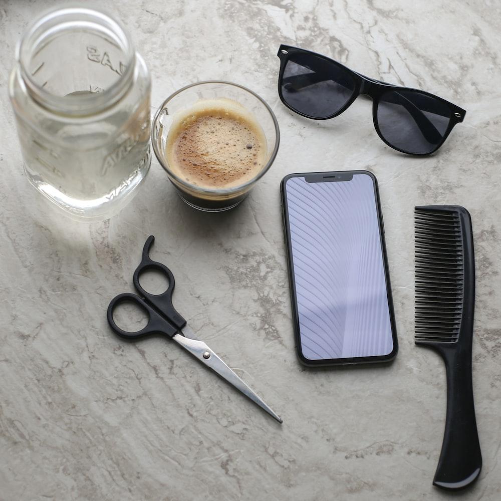black framed sunglasses beside clear glass mug and black handled scissors