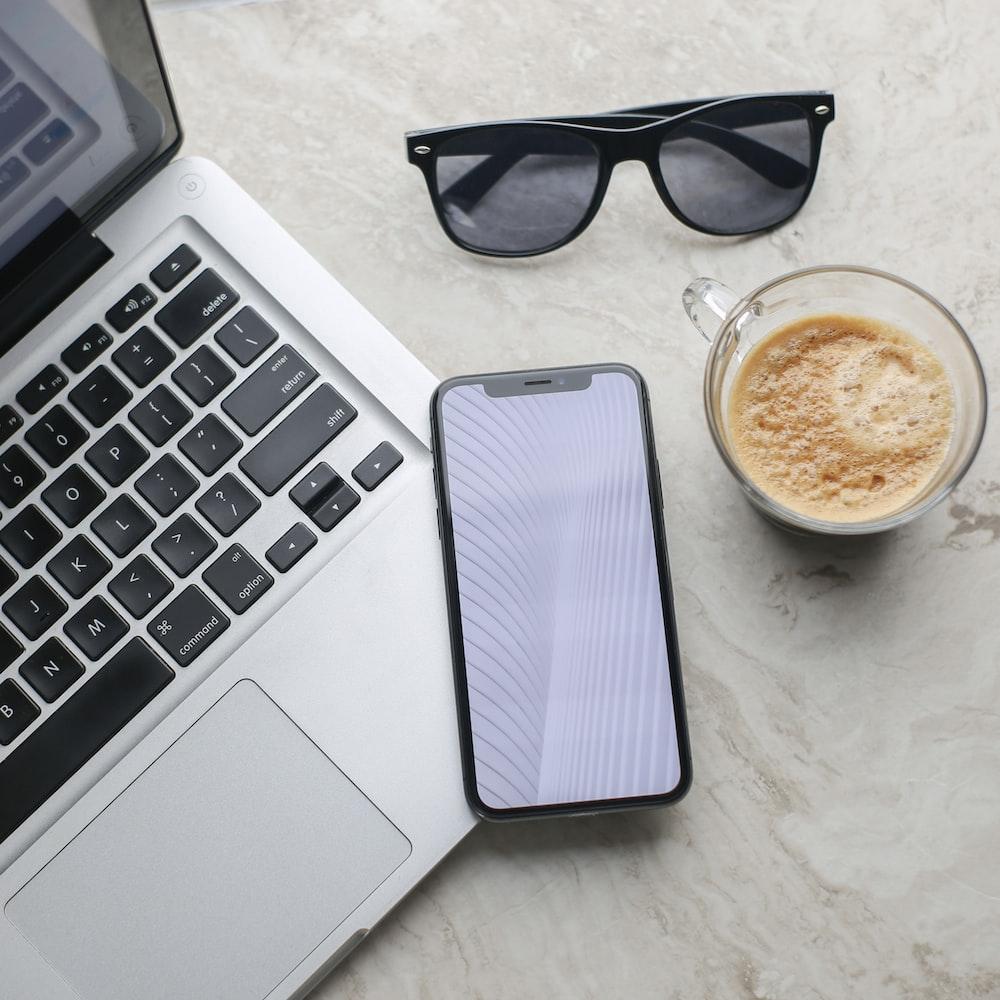 black framed sunglasses beside white ceramic mug and macbook pro