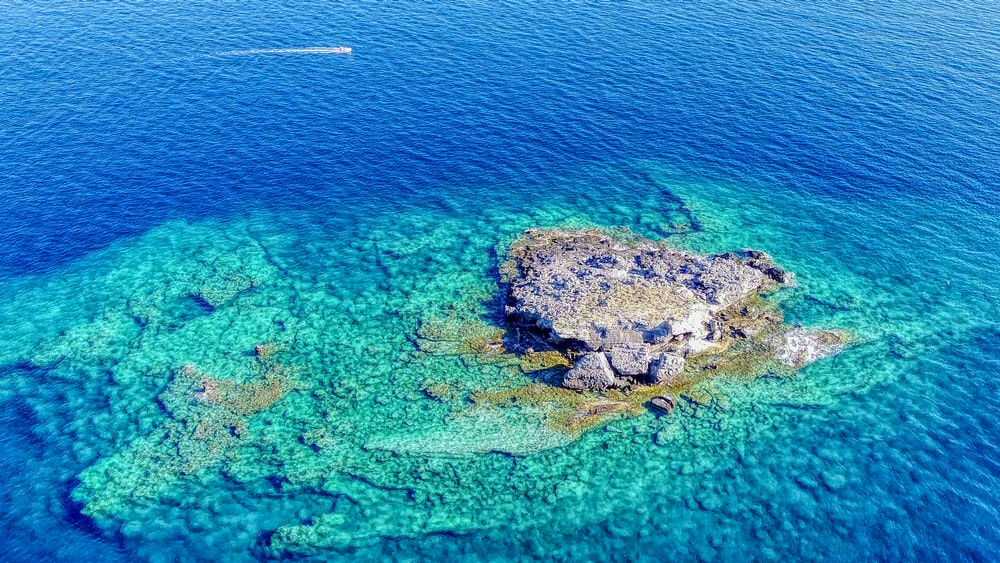 aerial view of green and brown island in the middle of blue sea