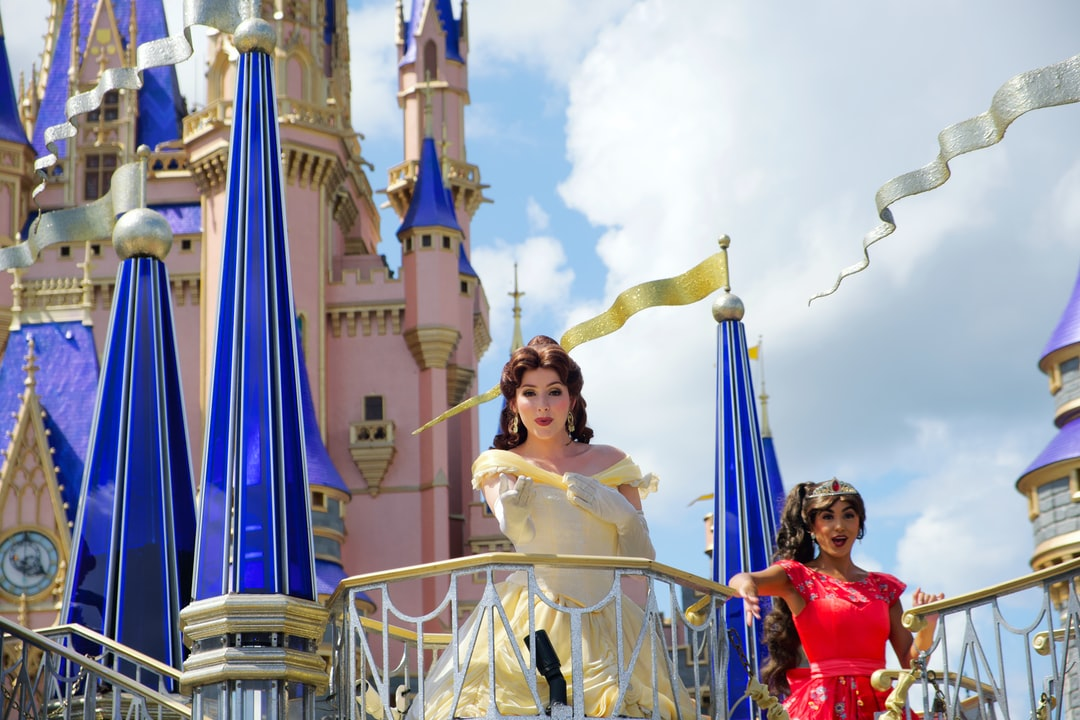 Princess blowing a kiss from a parade float in front of Cinderella Castle at Walt Disney World ✨