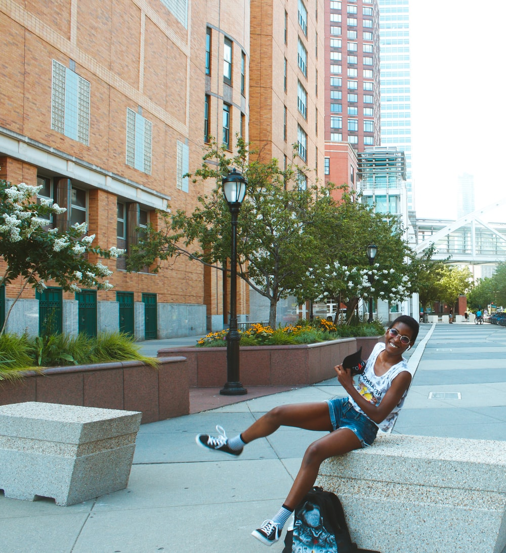 man in blue t-shirt and blue shorts sitting on gray concrete bench during daytime