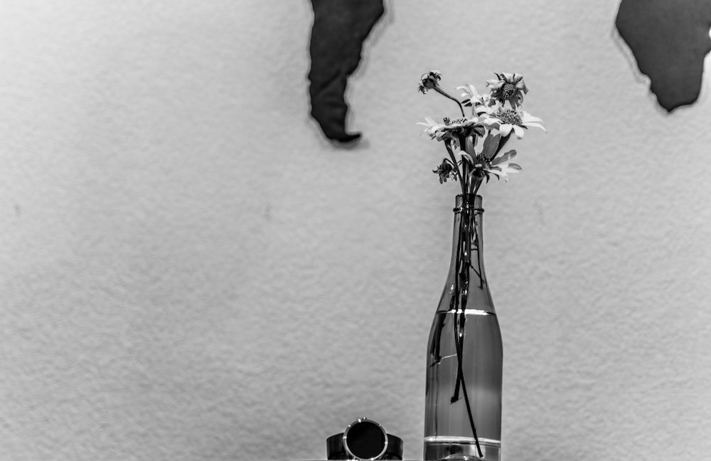 grayscale photo of person holding flower in glass vase