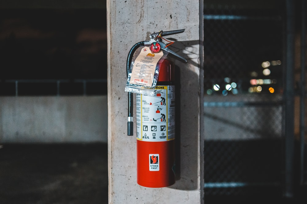 red fire extinguisher mounted on wall