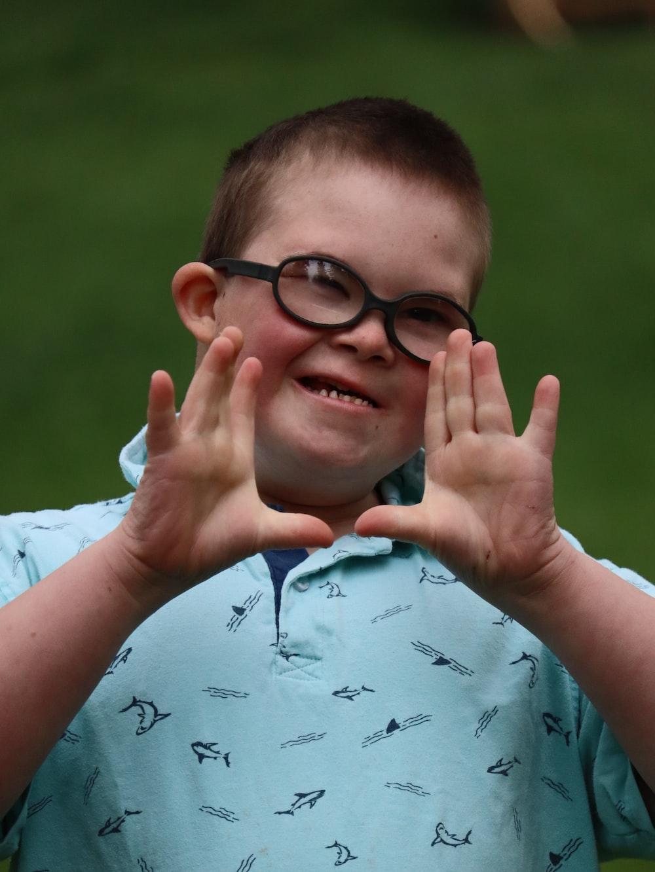 boy in white shirt wearing black framed eyeglasses