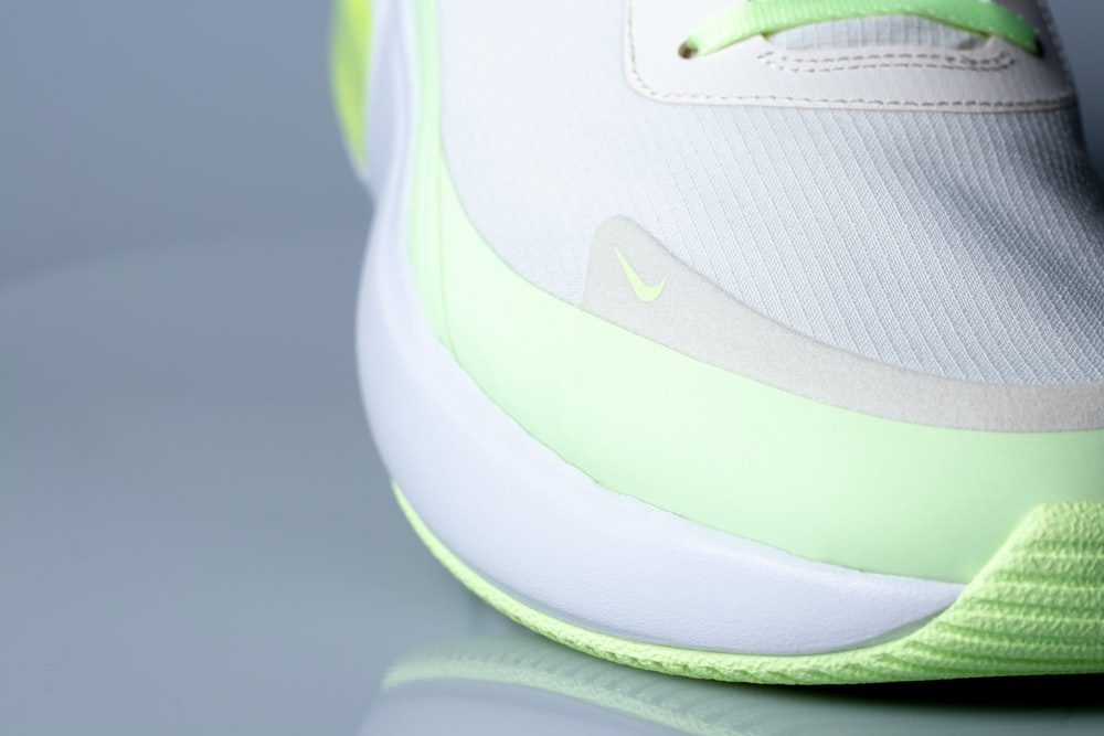 white and green nike athletic shoe