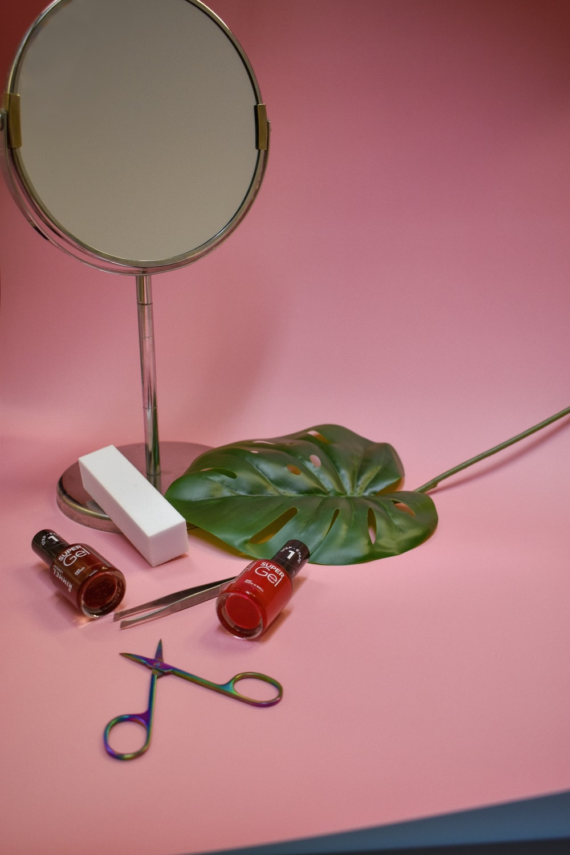 silver framed magnifying glass beside green plant