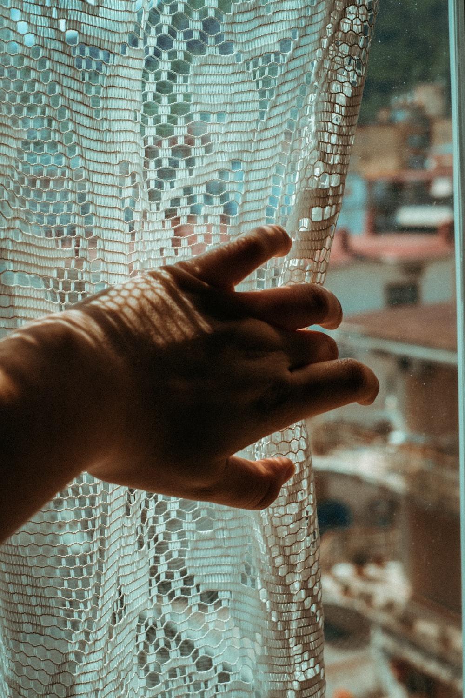 persons left hand on white mesh net
